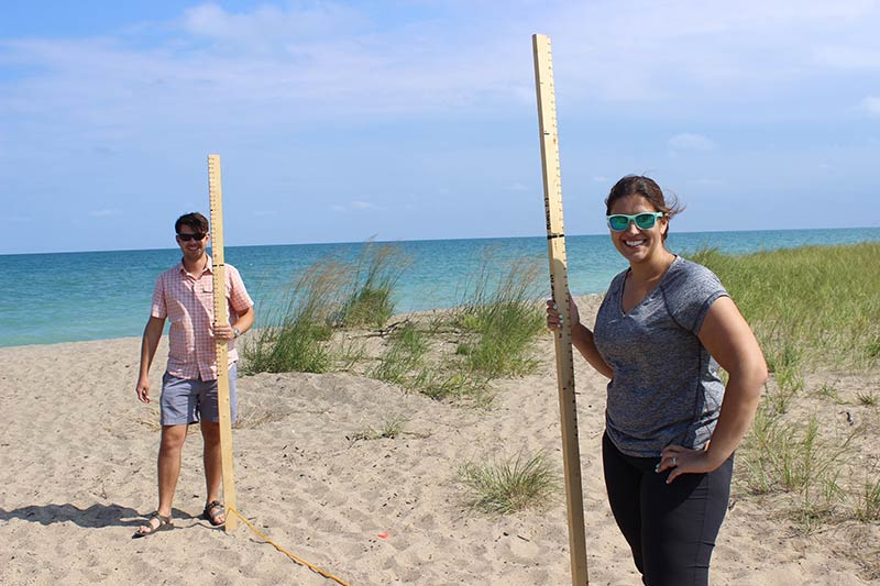 Two CMP staffers hold a measuring device on a Lake Michigan beach